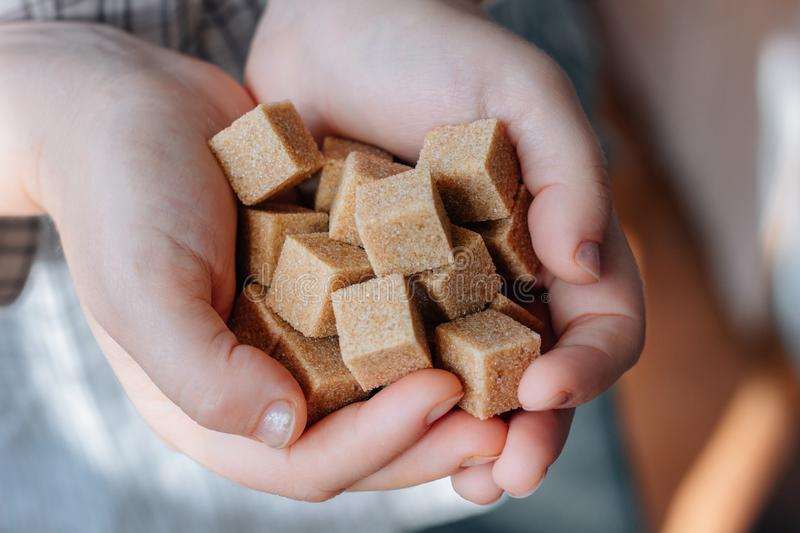Woman holds brown sugar cubes in hands. royalty free stock photos