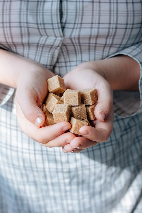 Woman holds brown sugar cubes in hands. stock photo