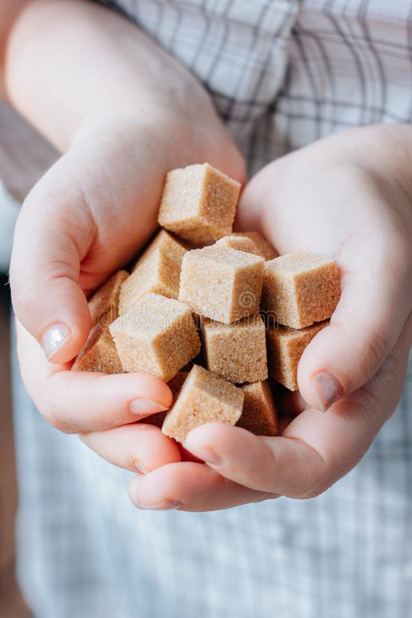 Woman holds brown sugar cubes in hands. royalty free stock image