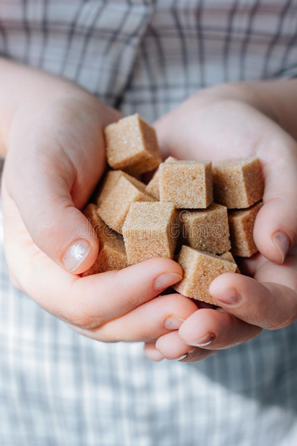 Woman holds brown sugar cubes in hands. stock photography