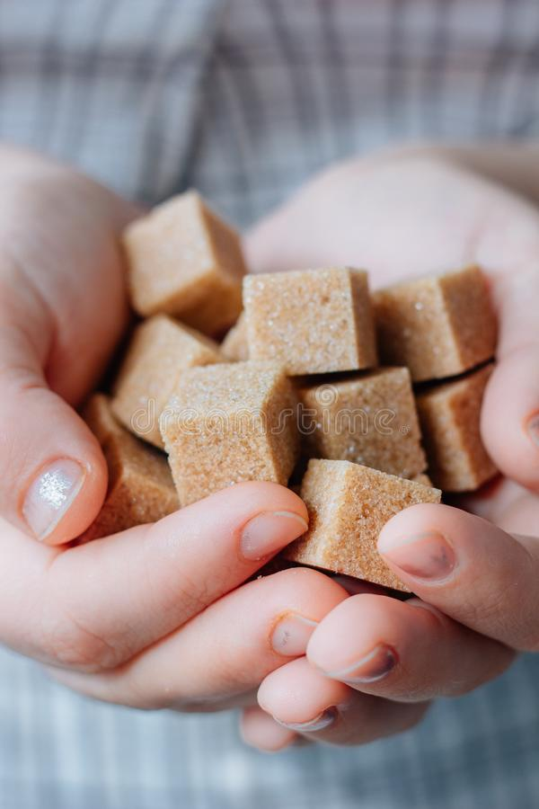 Woman holds brown sugar cubes in hands. stock images