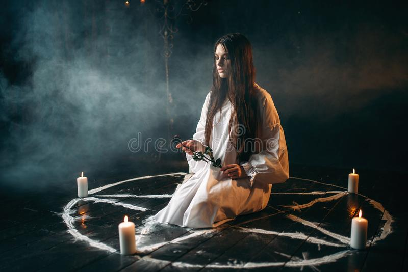 Woman holds burnt rose in hands, dark magic ritual. Young woman in white shirt holds burnt rose in hands, pentagram circle with candles, smoke all around. Dark royalty free stock photo