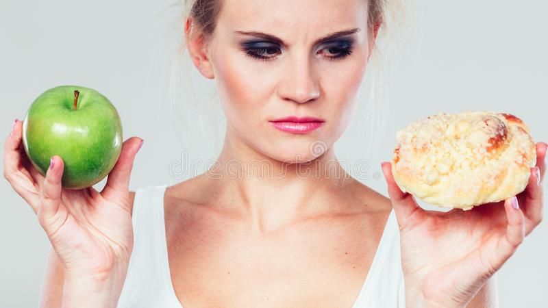Woman holds cake and fruit in hand choosing royalty free stock images