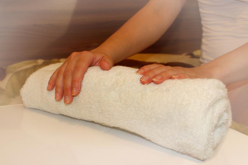Woman holds clean towels, hand brush and towel,  for spa treatments, vignette. Woman holds clean towels stock photo