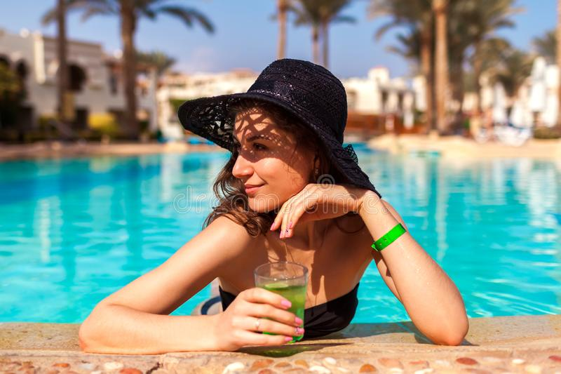 Woman holds a cocktail in hotel swimming pool. Summer vacation. All inclusive royalty free stock photos