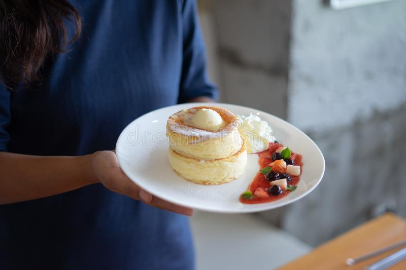 A woman holds a dish of two layers of puffy souffle pancakes in white dish with icing sugar, butter, whipped cream and mixed fresh. Berries in red berry sauce royalty free stock photos