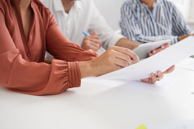 Woman holds a document in her hand as points stock photos