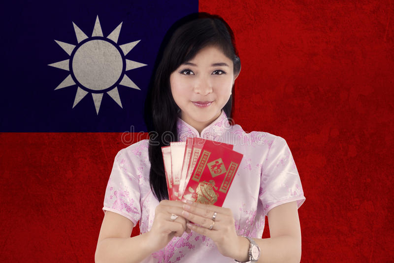 Woman holds envelope with flag of Taiwan. Beautiful young woman celebrate Chinese new year and holding envelope while wearing cheongsam dress with flag of Taiwan royalty free stock photo