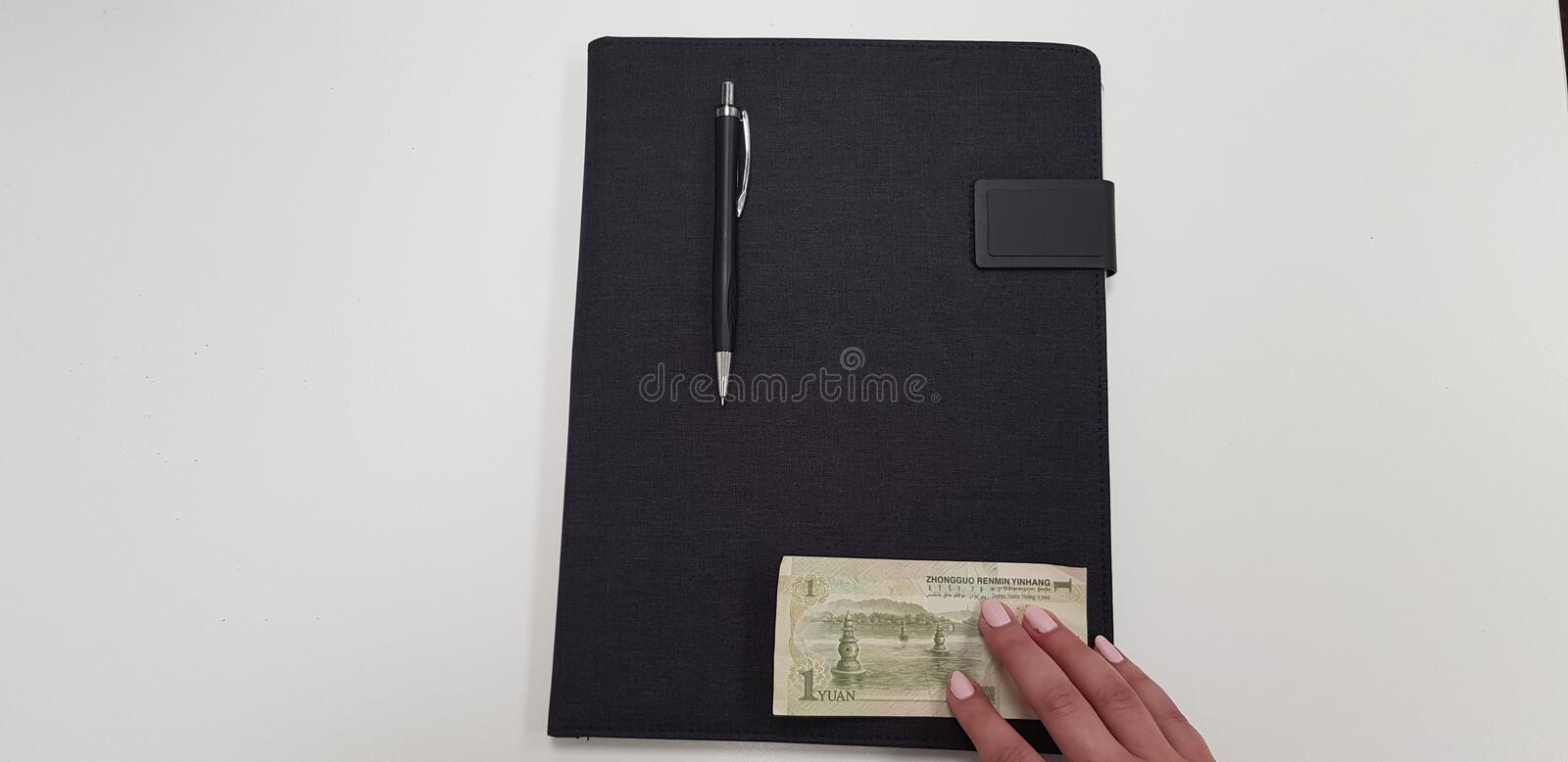 Woman holds fingers on one yuan banknote. Woman holds fingers on one yinhang banknote on black folder with pen on it bookmaker brokerage budget business china stock photography
