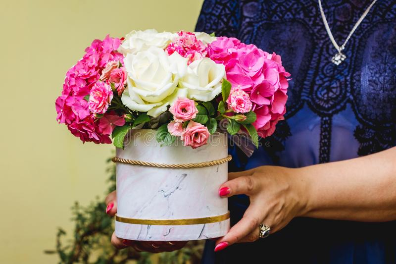 A woman holds a flower bouquet in her hands to greet brides_ royalty free stock photography