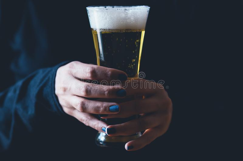 Woman holds a glass of beer. Isolated on dark background stock images