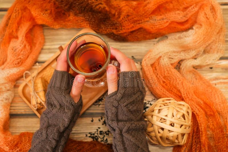 Woman holds glass cup of hot tea with cinnamon sticks. Winter cozy background, top view stock photos