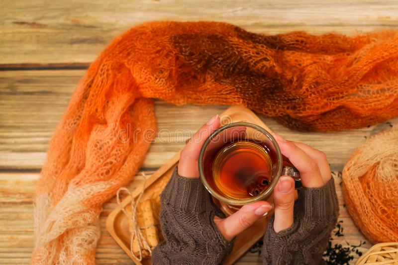 Woman holds glass cup of hot tea with cinnamon sticks. Winter cozy background, top view stock photography