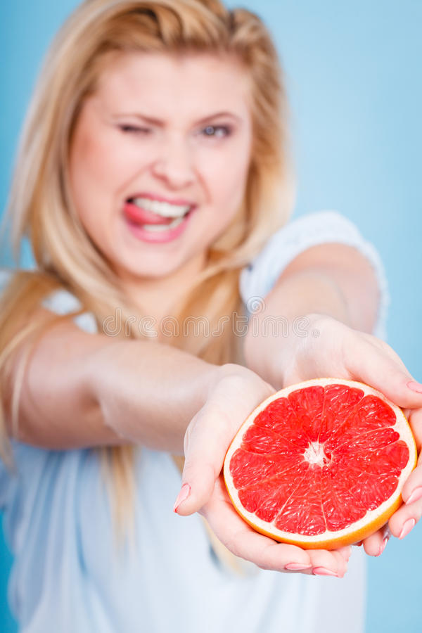 Woman holds grapefruit citrus fruit in hands royalty free stock photo