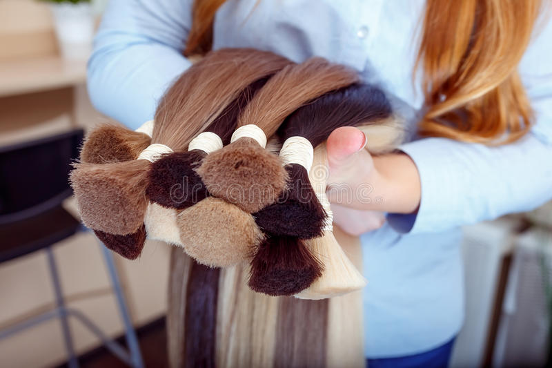 Woman holds hair extension equipment of natural hair. hair samples of different colors royalty free stock images