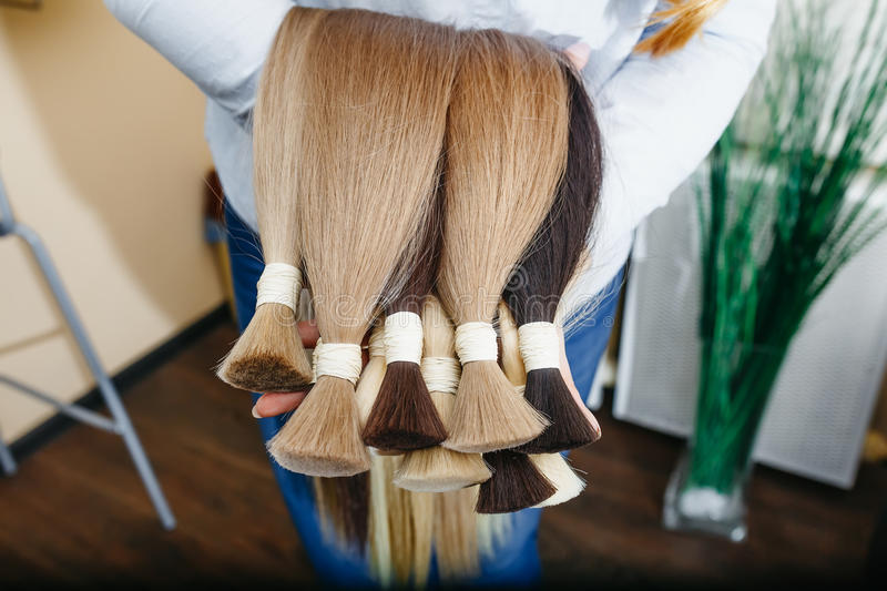 Woman holds hair extension equipment of natural hair. hair samples of different colors stock photography