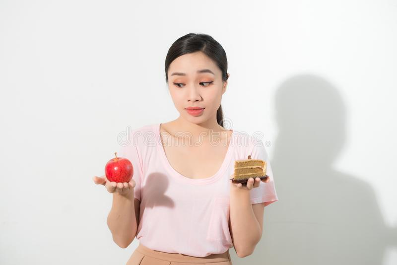 Woman holds in hand cake sweet and apple fruit choosing, trying to resist temptation, make the right dietary choice. Weight loss stock photos