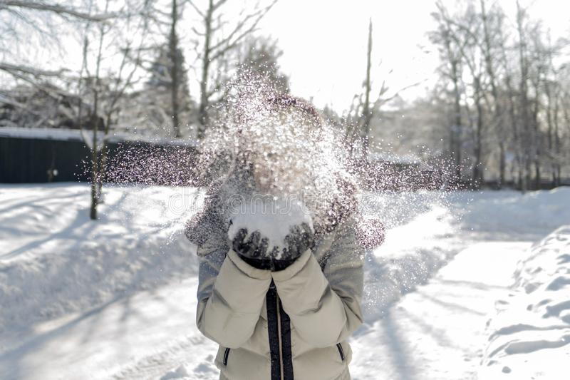 A woman holds a handful of snow in her hands and blows on it. Wi. Nter in the forest. The sun sparkles. Day, Russia stock photo