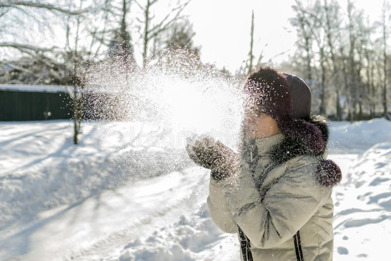 A woman holds a handful of snow in her hands and blows on it. Wi. Nter in the forest. The sun sparkles. Day, Russia stock photography