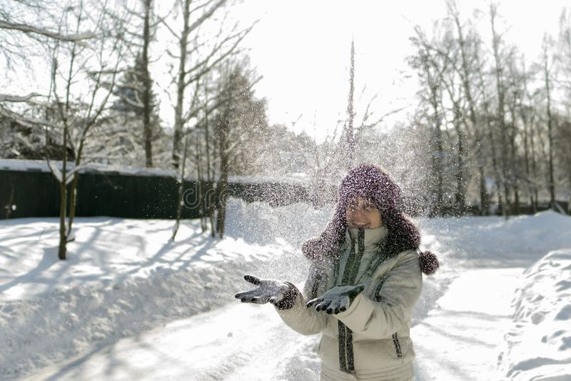 A woman holds a handful of snow in her hands and blows on it. Wi. Nter in the forest. The sun sparkles. Day, Russia royalty free stock photo