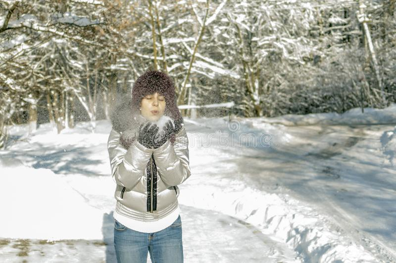 A woman holds a handful of snow in her hands and blows on it. Wi. Nter in the forest. The sun sparkles. Day, Russia stock images