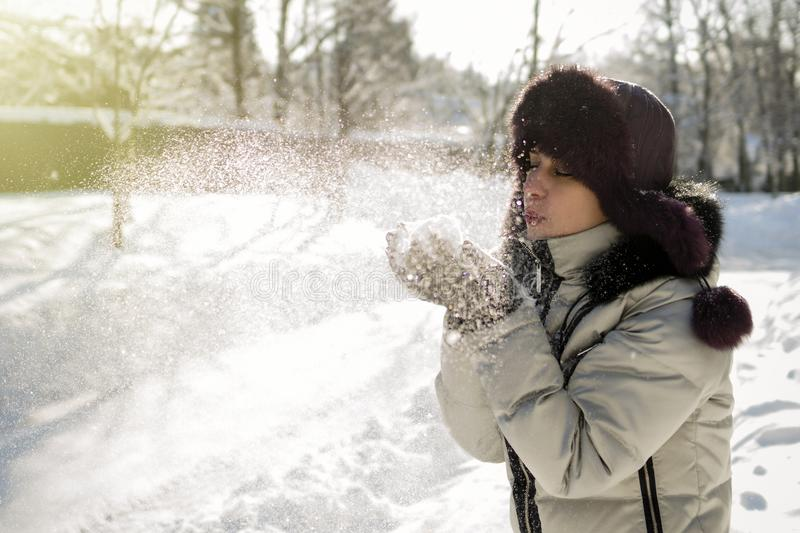 A woman holds a handful of snow in her hands and blows on it. Winter in the forest. The sun sparkles. Day, Russia royalty free stock images