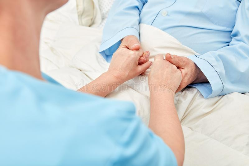 Woman holds the hands of a senior citizen in the hospice royalty free stock photos
