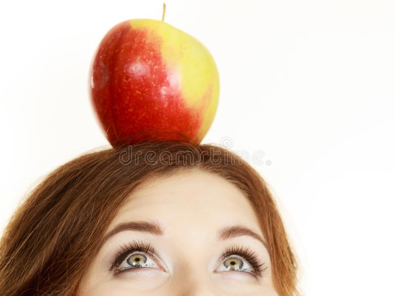 Woman holds on head apple fruit looking up royalty free stock photo