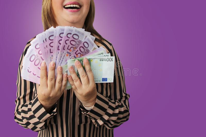 Woman holds in her hand a fan of paper currency notes of the European Union currency, 100 and 500 euros, a symbol of inheritance,. Salary, gift, win, copy space royalty free stock image