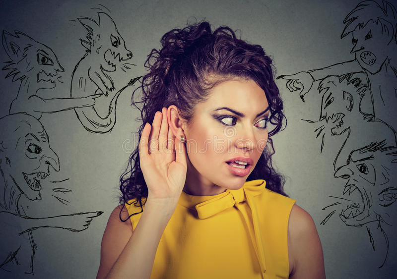 Woman holds her hand near ear and listens carefully to evil voices royalty free stock photography