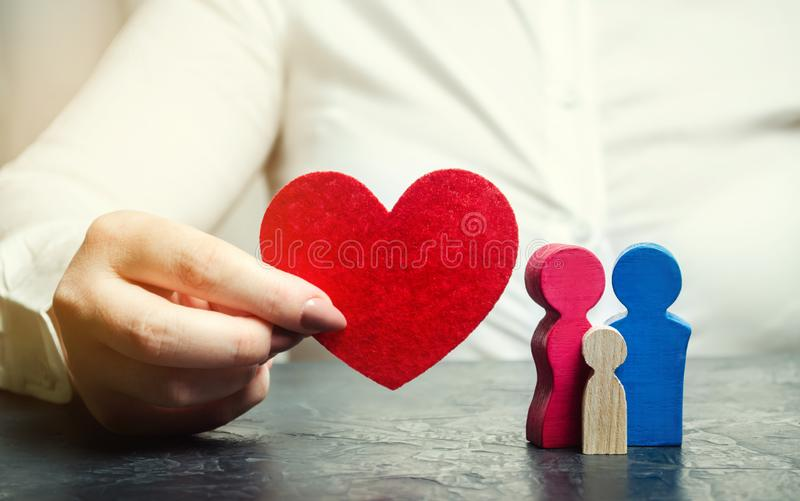 A woman holds in her hands a red heart near a miniature family. Concept of life and health insurance. Insurance agent services. stock images