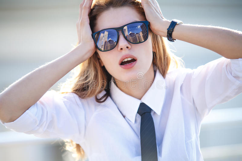 Woman holds her head with both hands (strong hangover). Business woman in glasses stock image