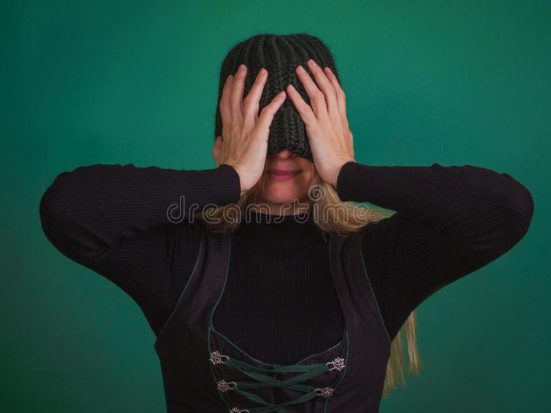 Woman with knitted stylish hat covering eyes. stock photography