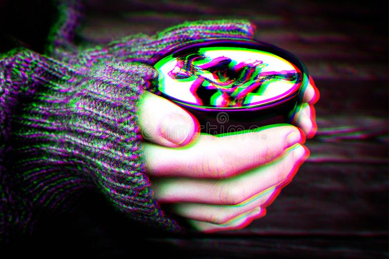Woman holds hot cup of coffee mocha with white foam and chocolate, warming your hands in warm knitted sweater. Anaglyph, glitch stock photos
