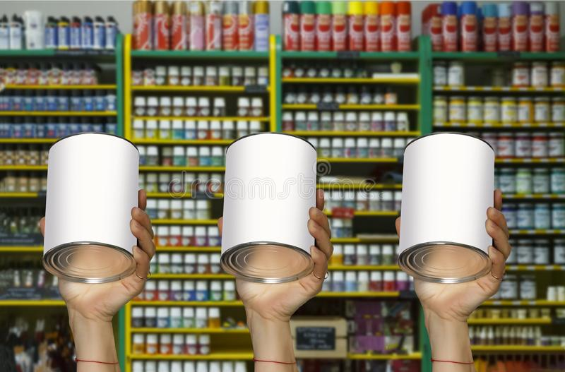 A woman holds a jar of paint and a brush in the hands of a shop window with various paints and building materials royalty free stock images