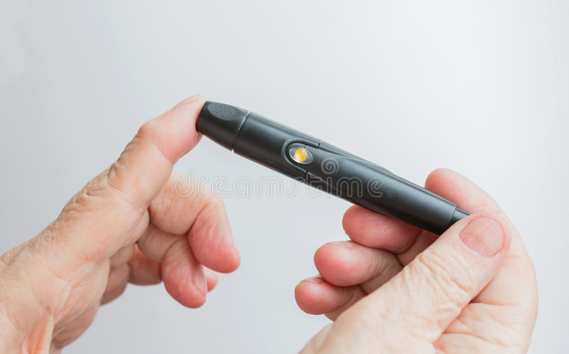A woman holds a lanset and pierces her finger to check the blood sugar level. Glucometer; white; Glucose; diabetic; analyze; sensitivity; exam; Illness stock image