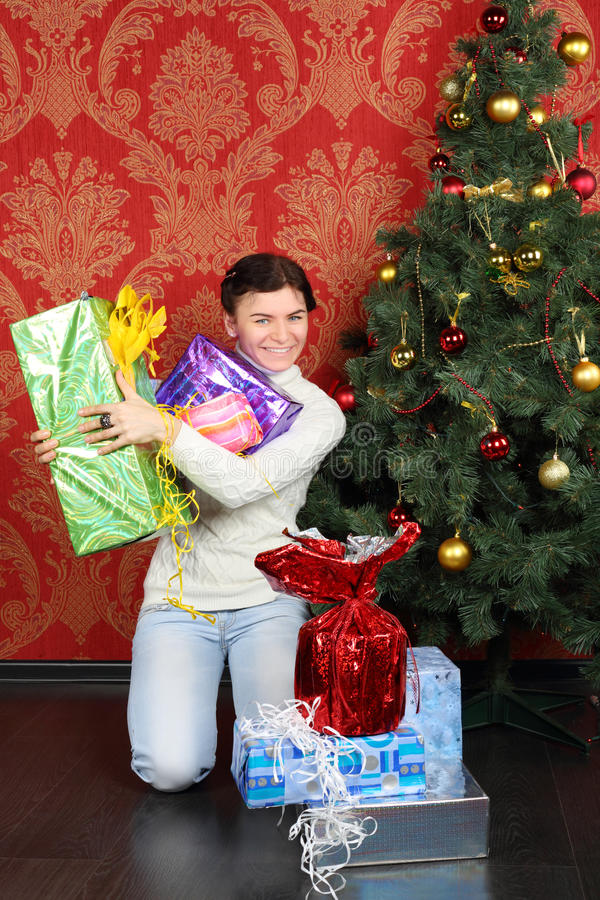 Woman holds many gifts at floor near Christmas tree and smiles. At home stock photo