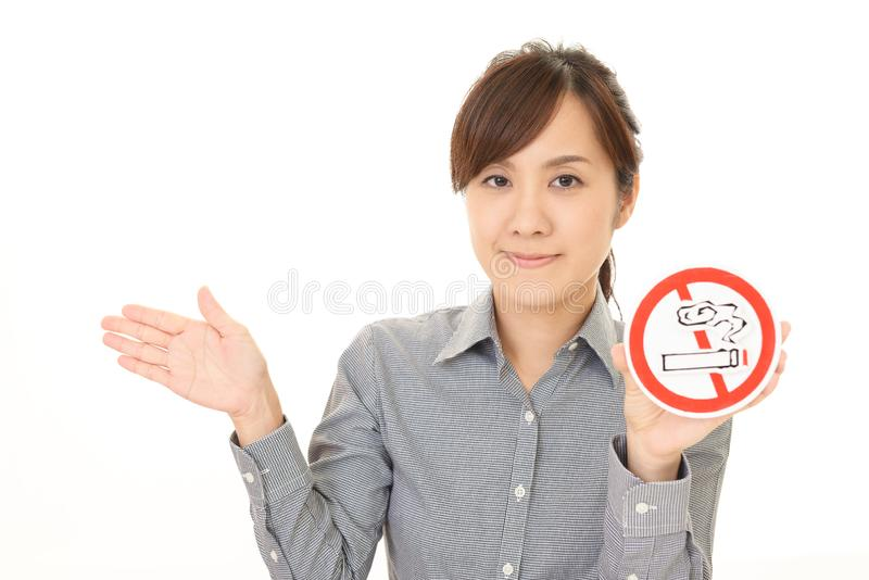 Woman holds non smoking sign. Woman with a non smoking sign stock photography