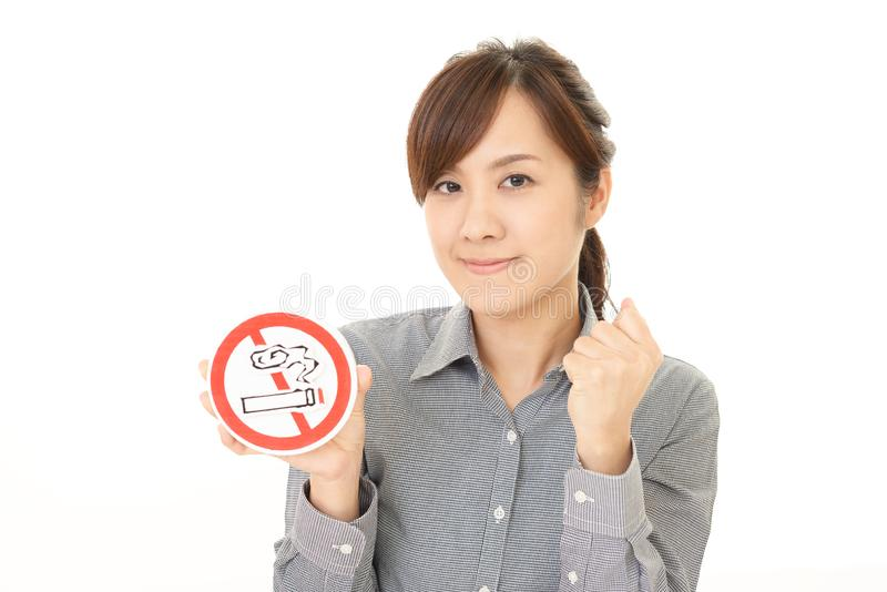 Woman holds non smoking sign. Woman with a non smoking sign stock images