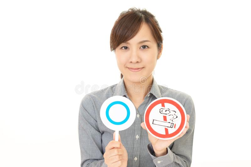 Woman holds non smoking sign. Woman with a non smoking sign stock image