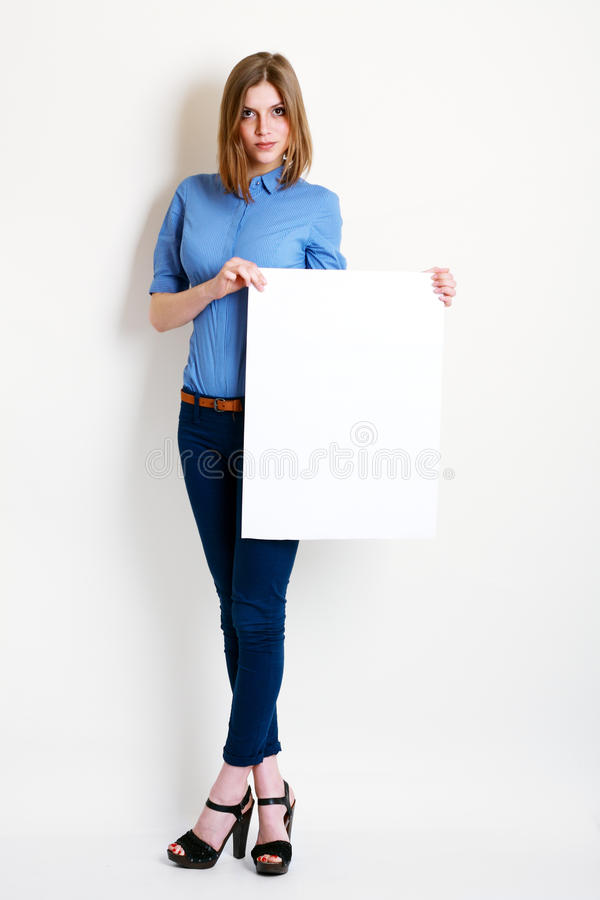 Woman holds out a big blank card. A beautiful woman holds out a big blank card on white background royalty free stock photo