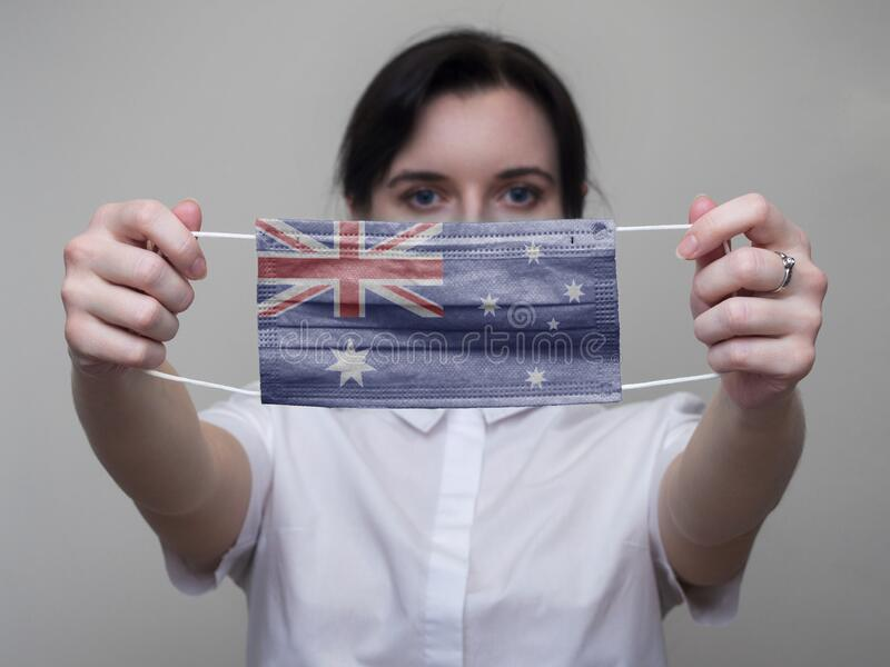 Woman holds out in her hands a medical mask with the image of the flag of Australia. Coronavirus COVID-19.  royalty free stock image