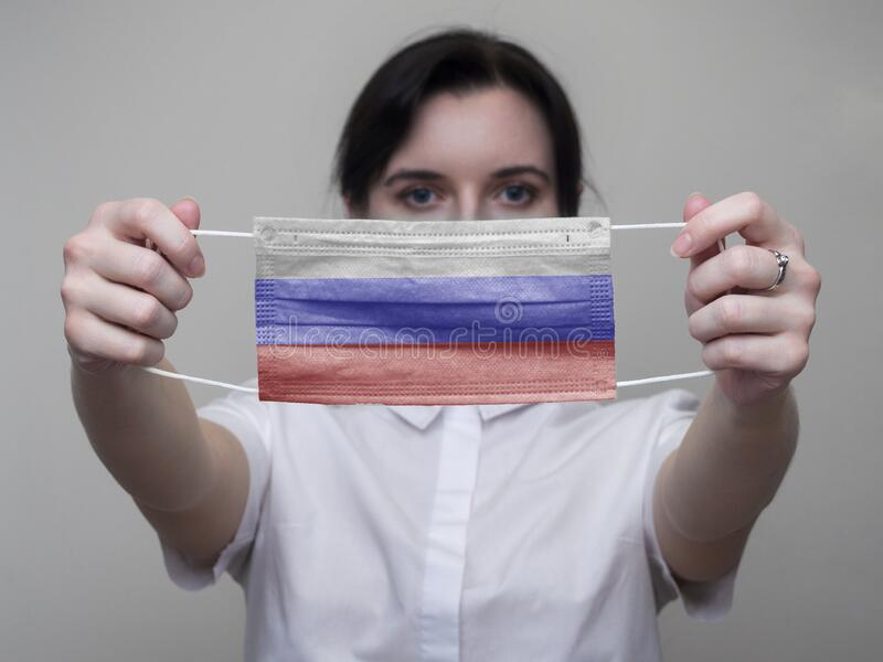 Woman holds out a medical mask with the image of the flag of Russia in her hands. Coronavirus COVID-19.  stock photos