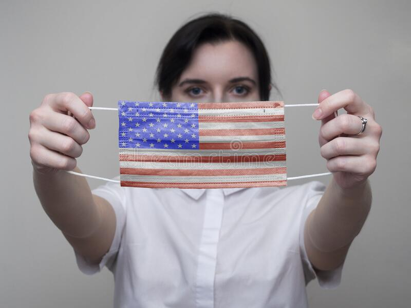 A woman holds out a Medical mask with the image of the flag of the United States of America USA in her hands. Coronavirus COVID-. 19 stock images