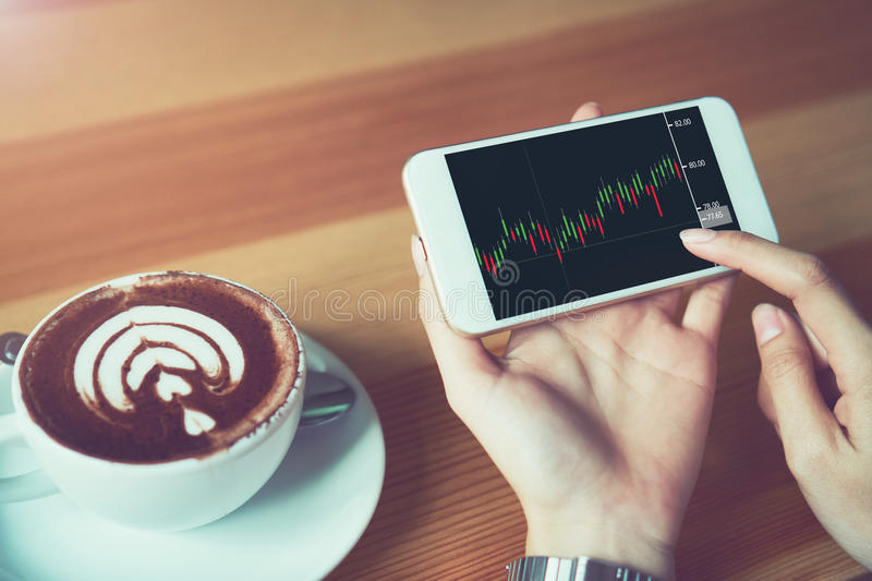 The woman holds the phone on a table with a graphical screen to invest the stock`s value. Investment concepts that rely on decisi. On-making information, vintage stock images