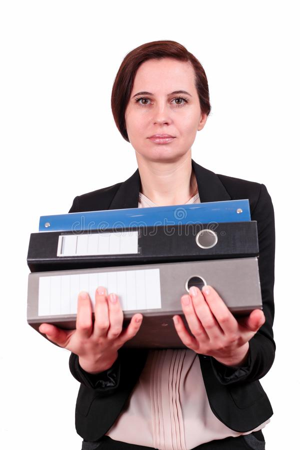 The woman holds a pile of folders. The business woman the brunette keeps a pile of folders with documents in a jacket, on the isolated white background. A stock photos
