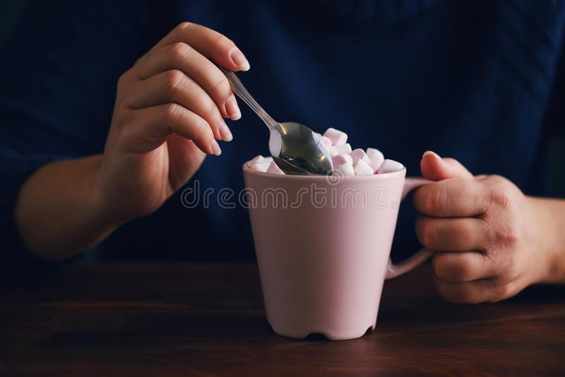 Woman holds pink mug of hot chocolate and marshmallow stock image