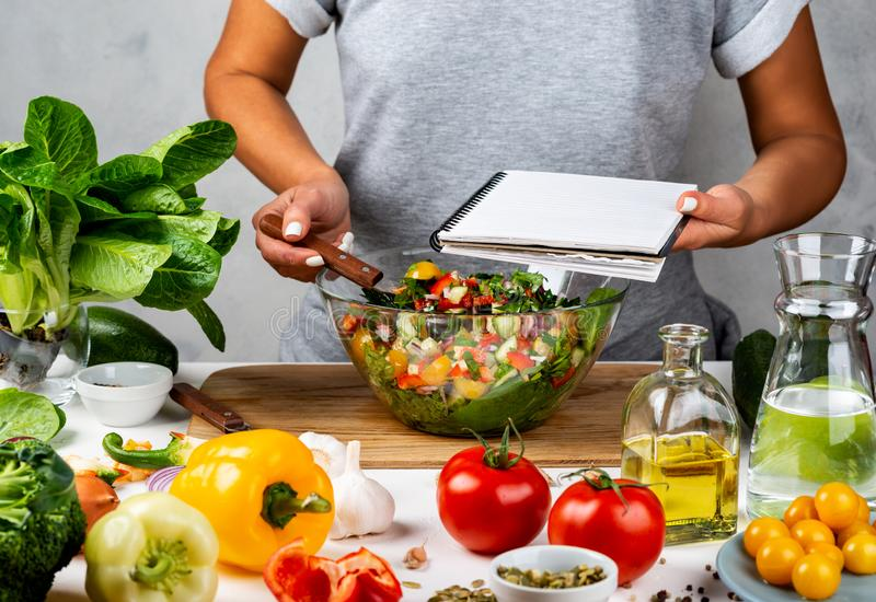 Woman holds recipe book with place for text in her hand and cooking healthy food in the kitchen. Healthy vegan food. Clean eating, dieting royalty free stock photography