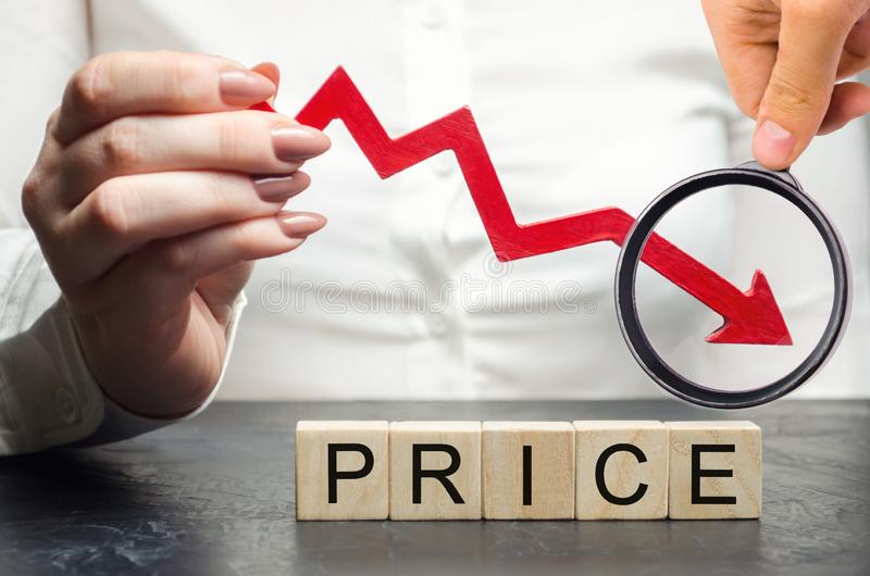 A woman holds a red arrow down over wooden blocks and the word Price. Concept of falling market value. Promotions and sale. Reduced prices for housing and food stock photo