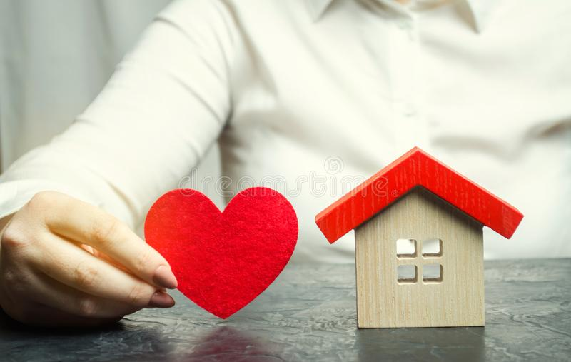 A woman holds a red heart near the wooden house. Insurance agent services. Property insurance concept. Protection of housing. stock images